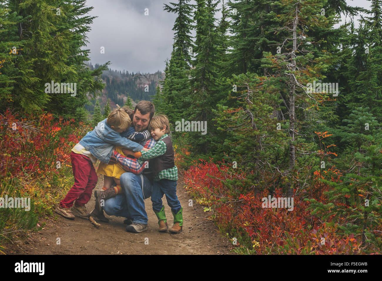 Tres hijos abrazando a su padre Imagen De Stock