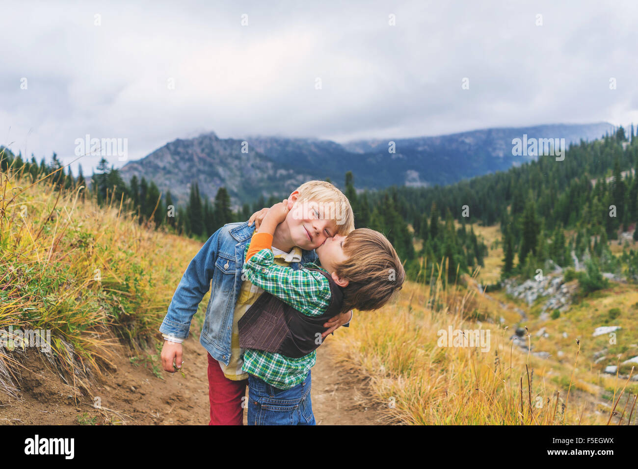 Dos hermanos, abrazos y besos en camino de montaña. Imagen De Stock