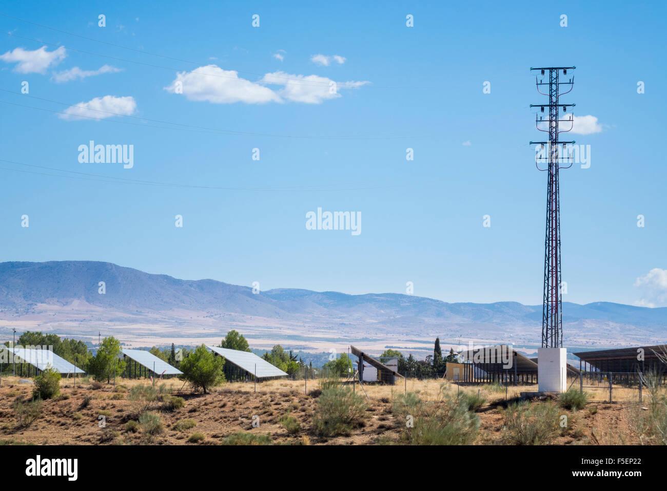 Fila de paneles solares y electricidad pilono en en granja solar en el sur de España Imagen De Stock