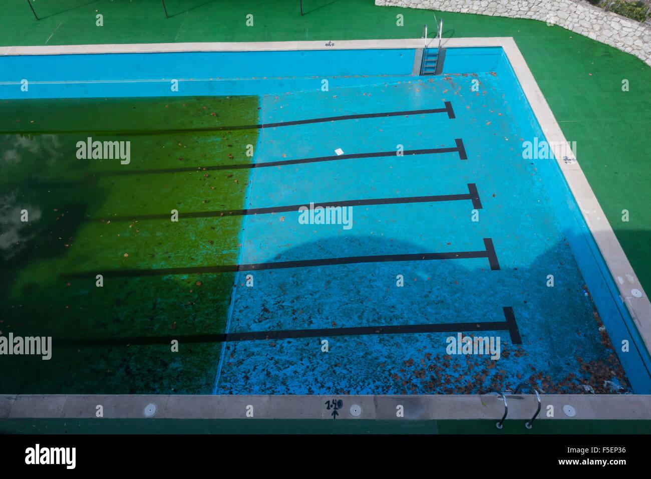 Sucio viejo abandonó la piscina pública lleno hasta la mitad con algas verdes debido al agua estancada Imagen De Stock