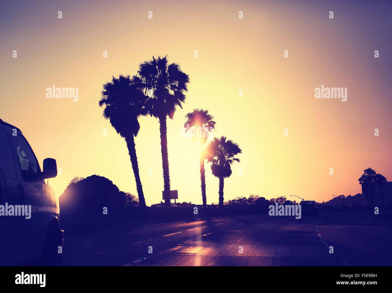 Imagen estilizada vintage de carretera contra el atardecer, California, USA. Foto de stock