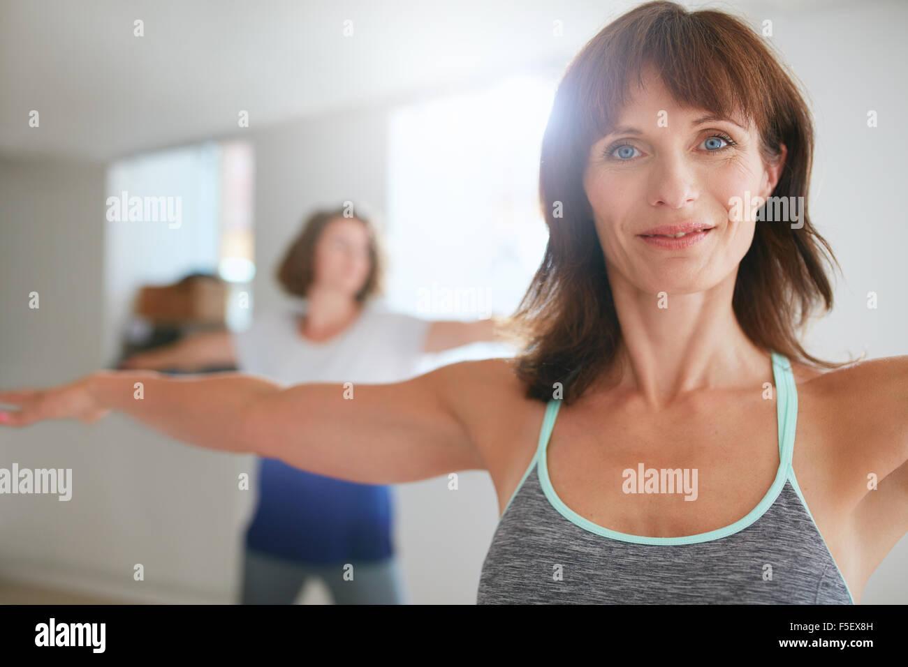 Dos mujeres haciendo estiramientos y yoga entrenar en el gimnasio. Entrenador femenino con su estudiante en segundo Imagen De Stock