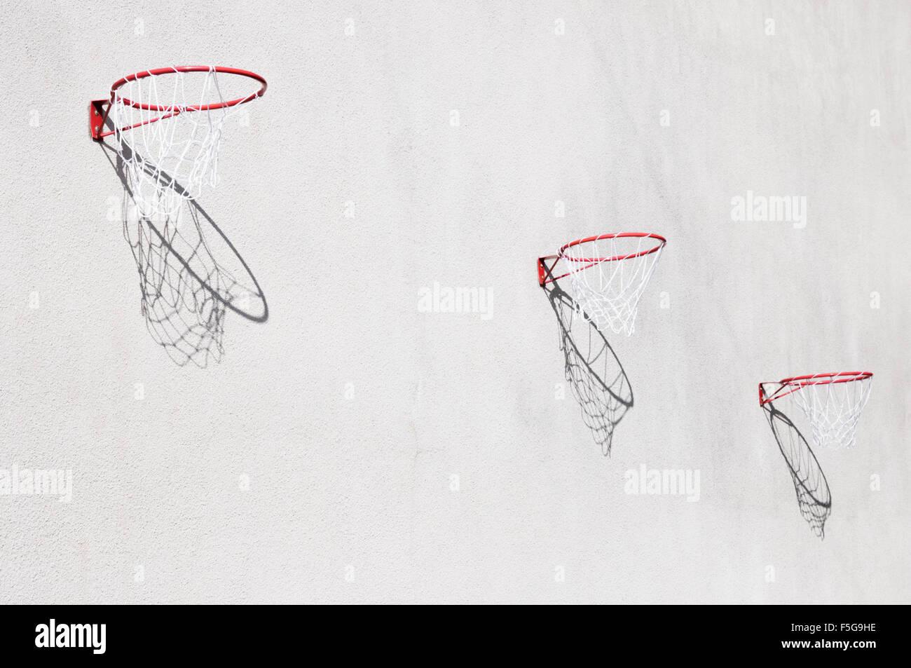 Tres aros de baloncesto con sombras en una pared. Imagen De Stock