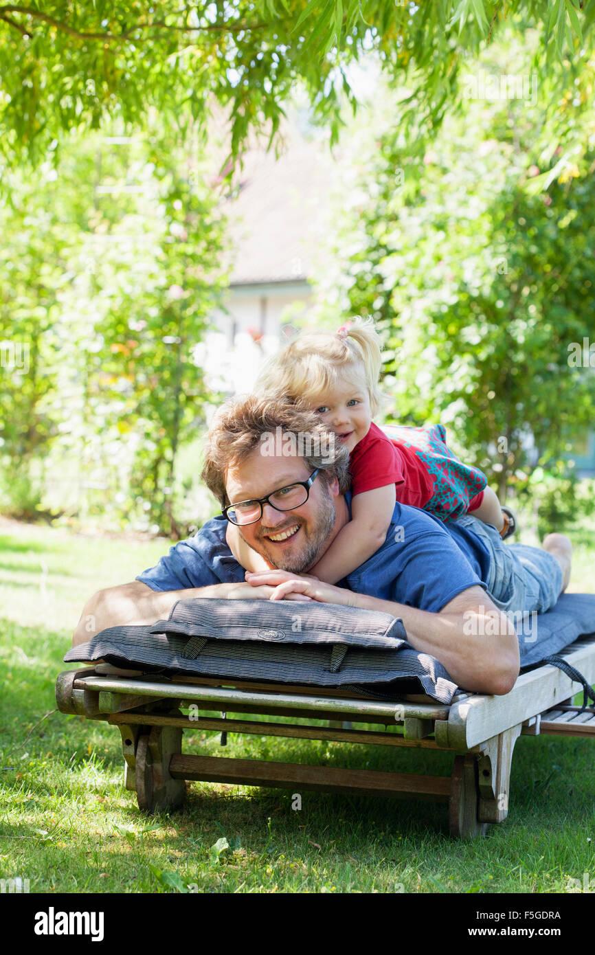 Suecia, Skane, Mossby, retrato de la hija con el padre tumbado en la tumbona. Imagen De Stock