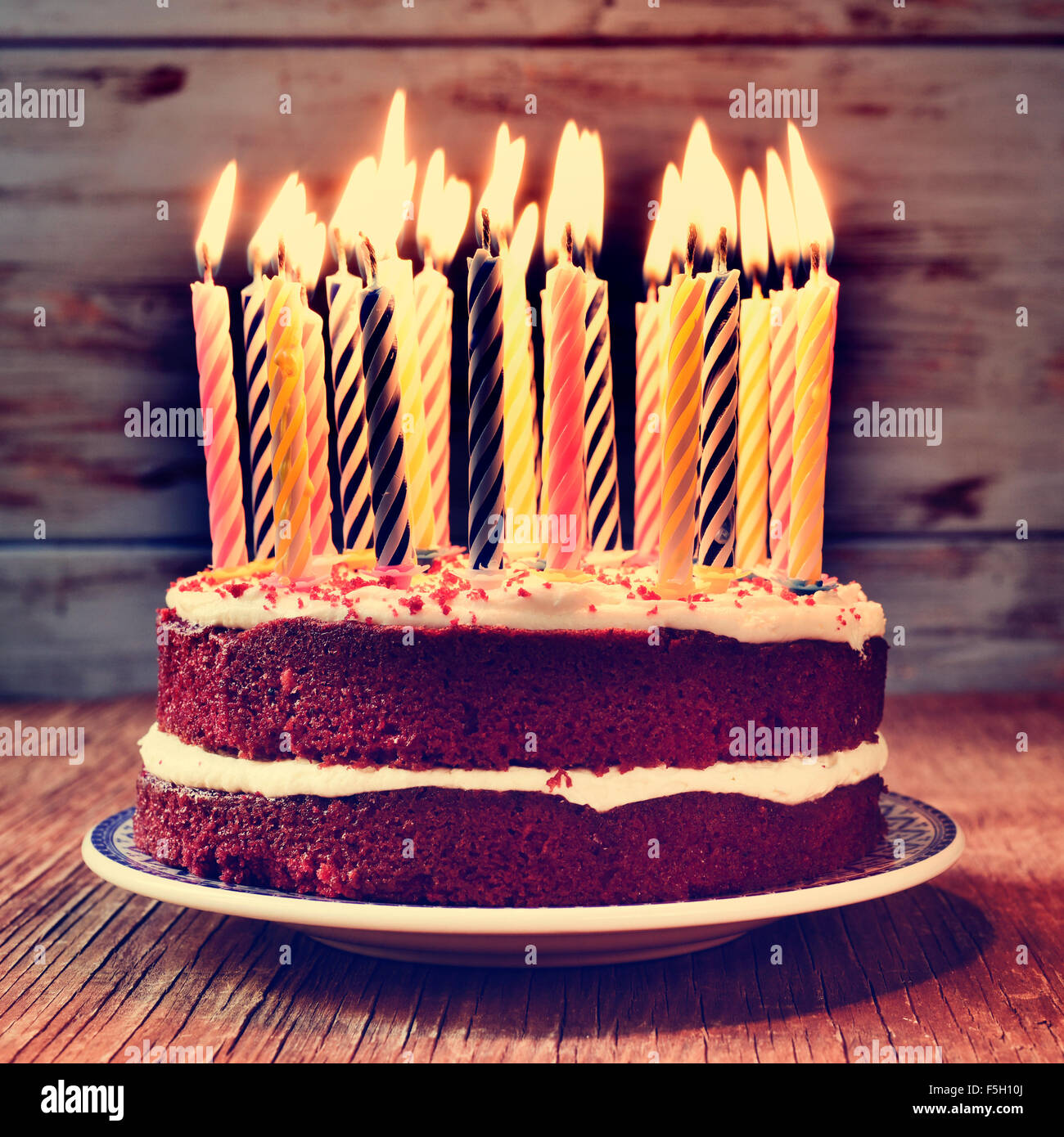 Un pastel coronado con algunas velas antes de soplar la torta, sobre una tabla de madera rústica, con un efecto Imagen De Stock