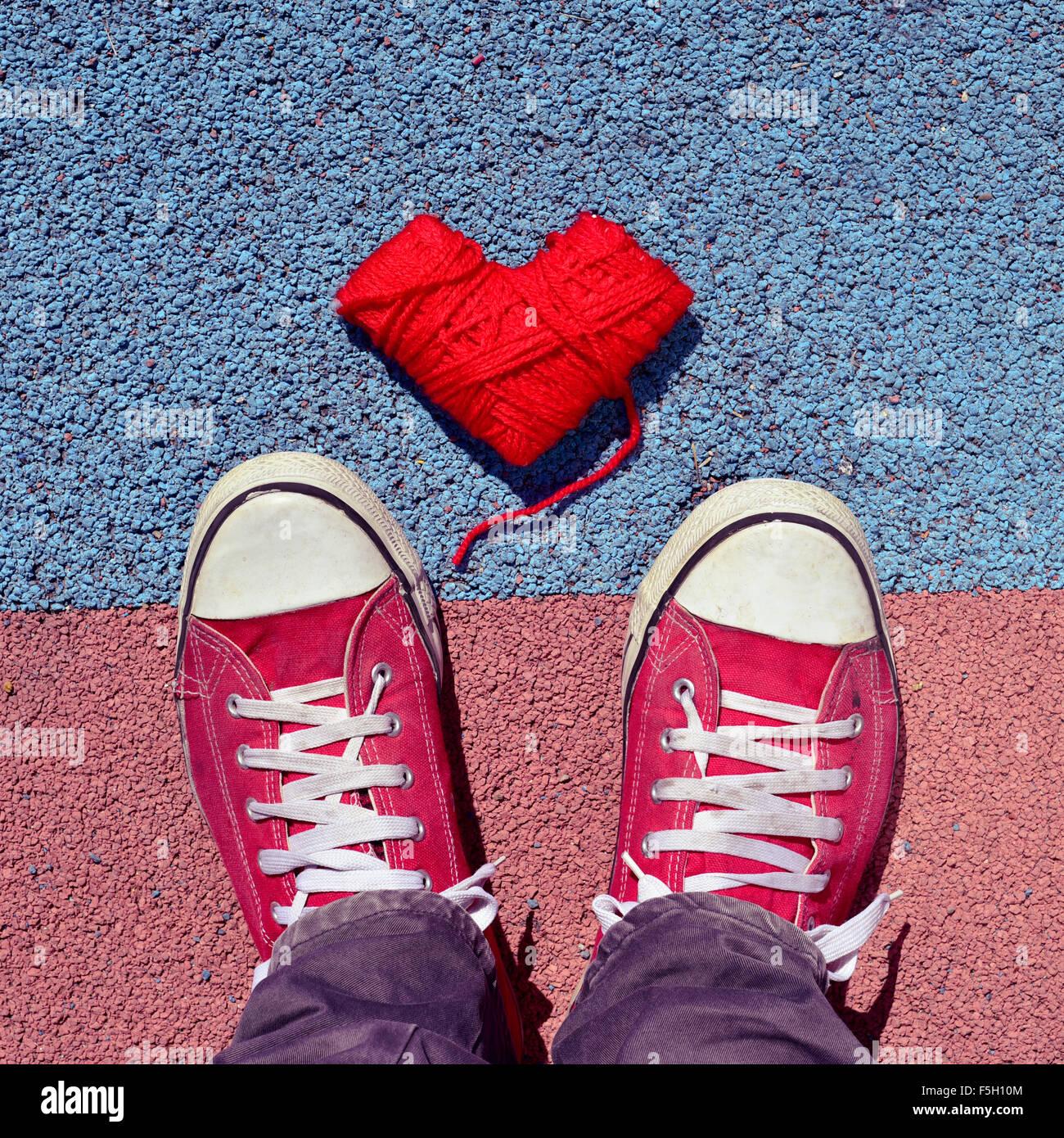 Disparo de alto ángulo de una bobina con forma de corazón rojo de lana y los pies de un hombre vestido con zapatillas Foto de stock