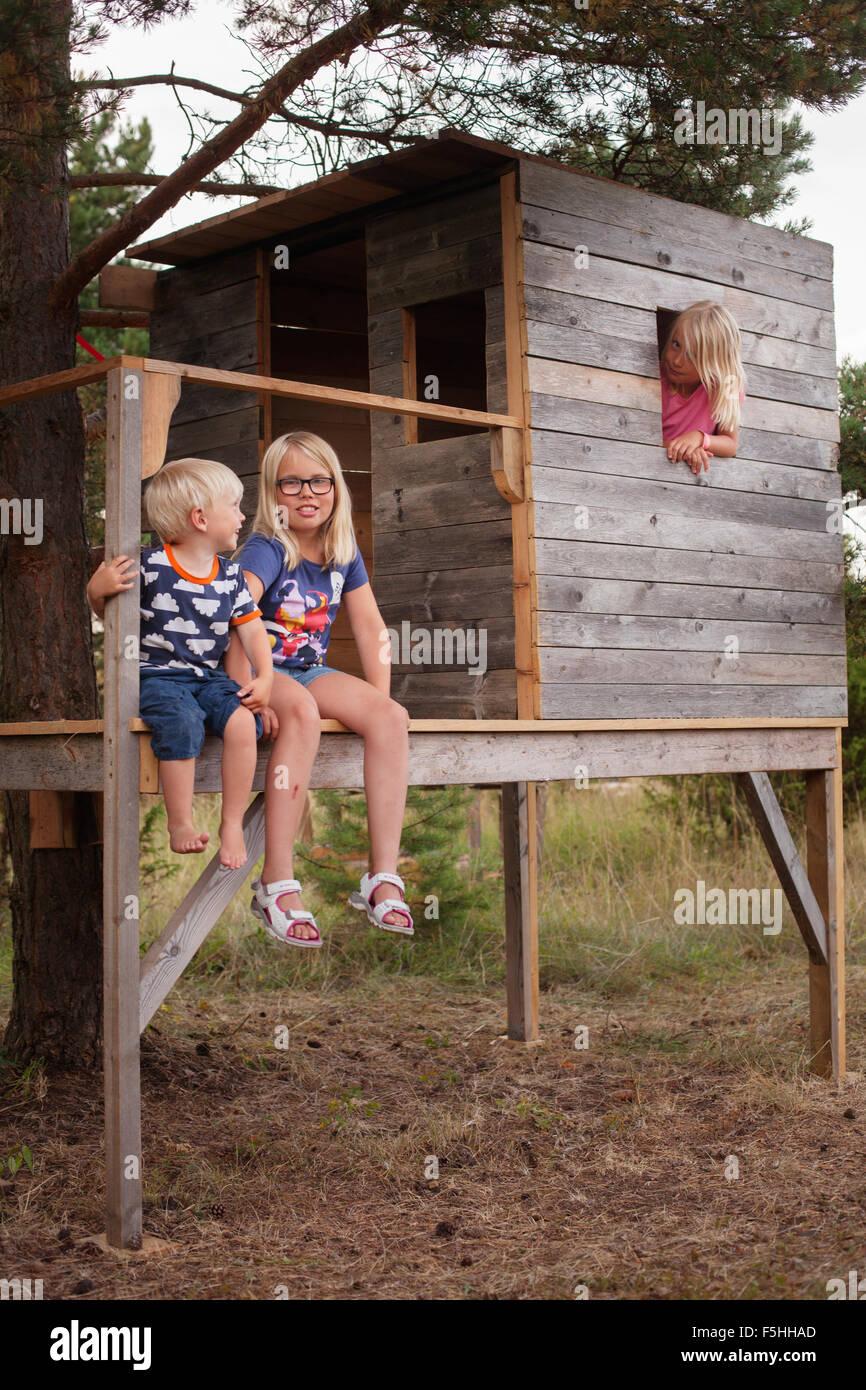 Suecia, Gotland, Faro, Boy (2-3) y hermanas (8-9, 10-11) sentado en el porche de una casa en el árbol Imagen De Stock