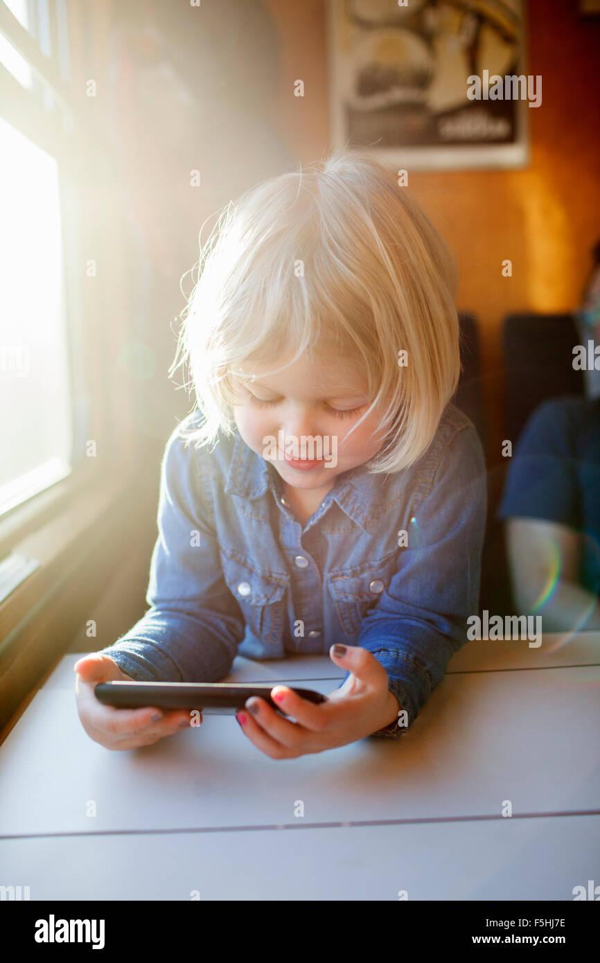 Suecia, Chica (2-3) utilizando el teléfono inteligente en tren Imagen De Stock