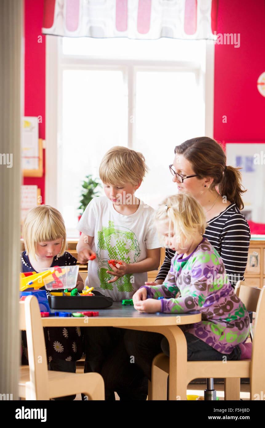 Suecia, niños jugando con el maestro en kindergarten. Imagen De Stock