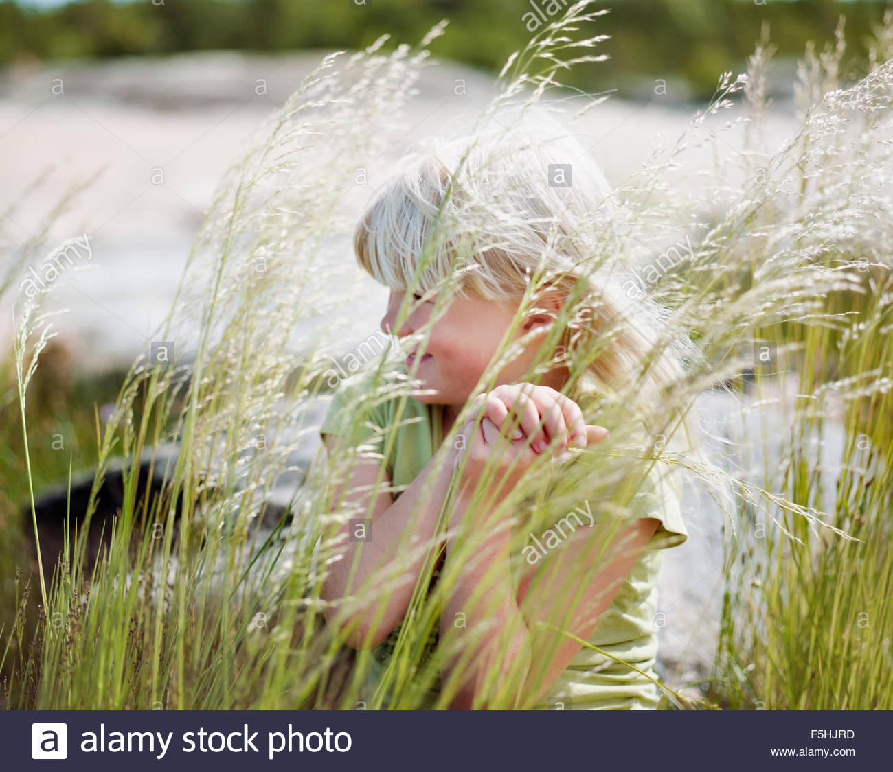 Suecia, archipiélago de Estocolmo, Uppland Arholma, Chica (6-7) detrás de la hierba alta Imagen De Stock