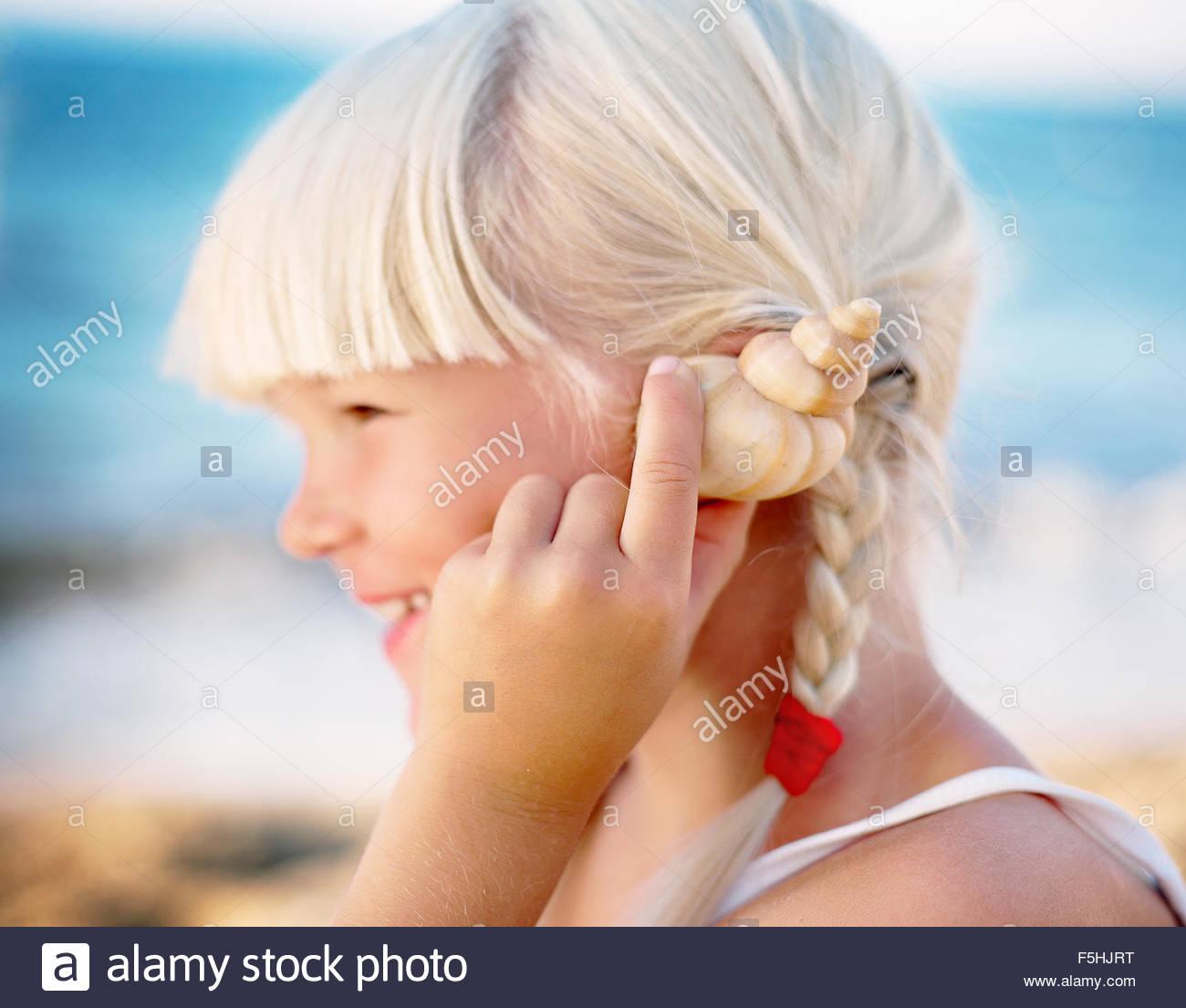 Grecia, Creta, Chica (6-7) sujetando el Seashell cerca al oído Imagen De Stock