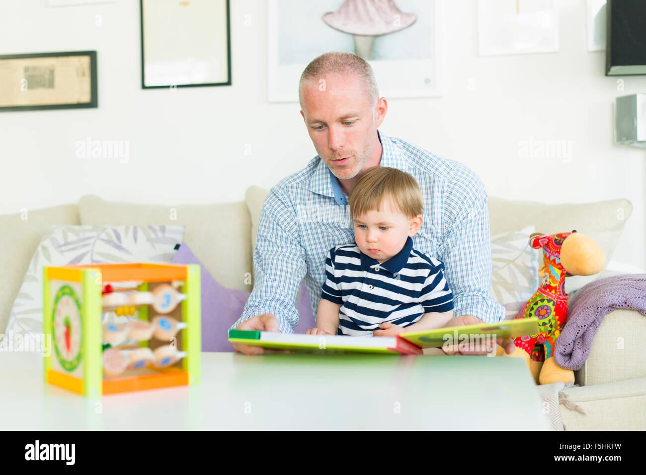 Suecia, hombre leyendo a su hijo (18-23 meses) Foto de stock