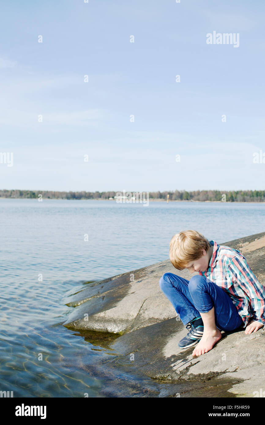 Suecia, Uppland Oregrund, Boy (8-9) Comprobación de la temperatura del agua del mar con su pie. Foto de stock