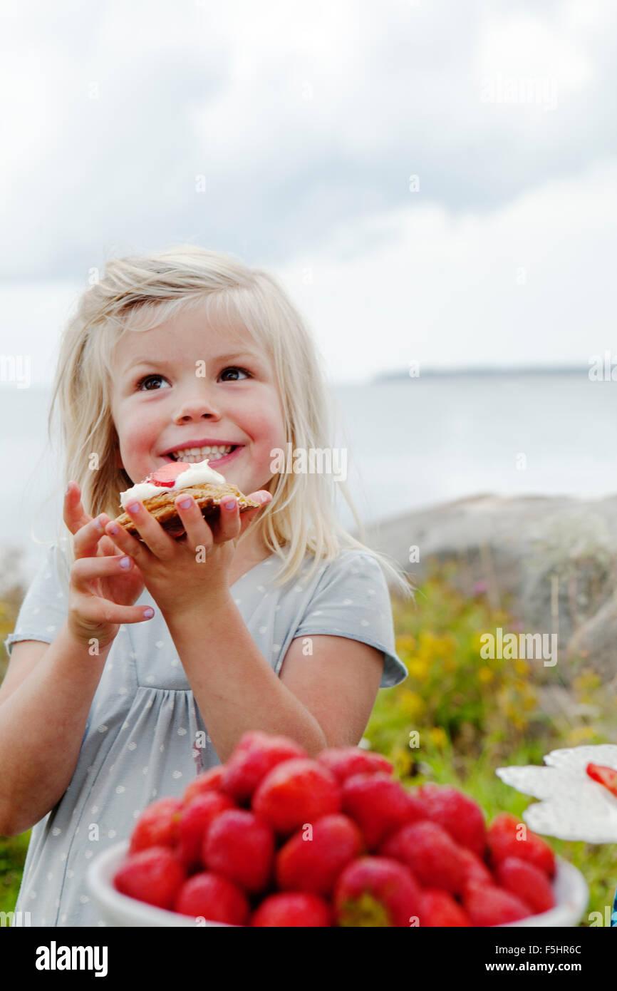 Suecia, Uppland Roslagen, Chica (6-7) comer afuera de postre de fresa Imagen De Stock