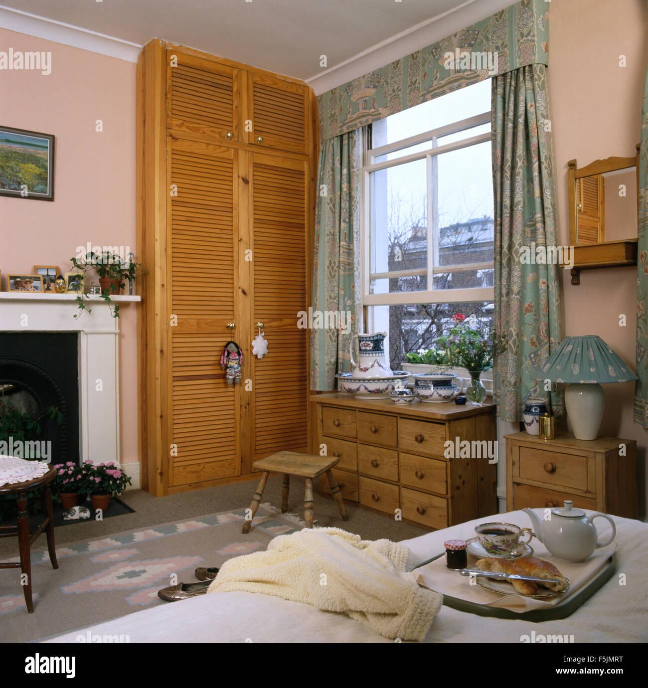 Las puertas del Louvre en armario junto a abrir en una ventana de guillotina 90 adosado dormitorio con una bandeja Foto de stock