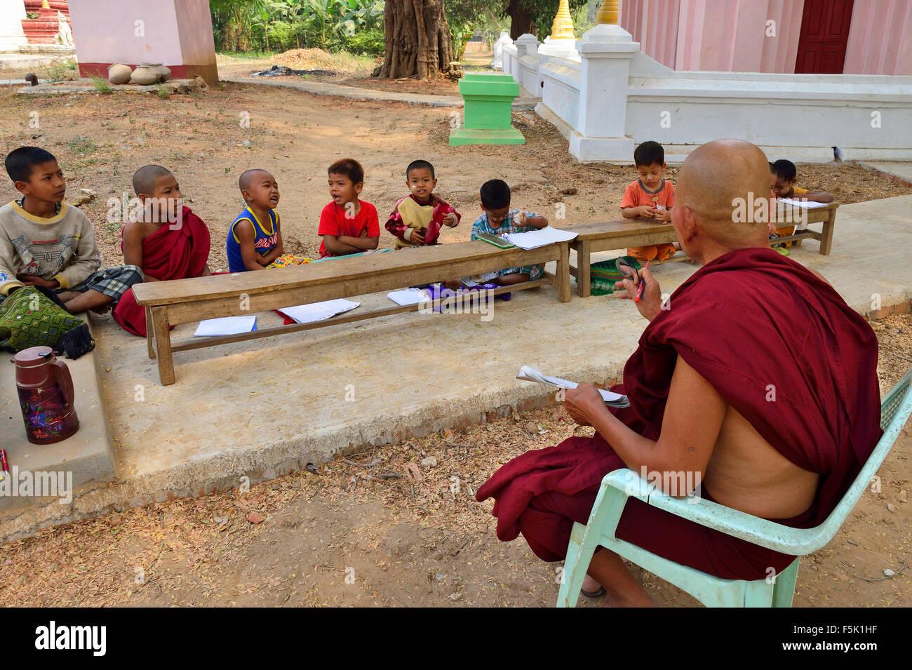 Monje budista enseñar lecciones escolares al aire libre en los jardines de estupas y templos cerca de Mandalay, Foto de stock
