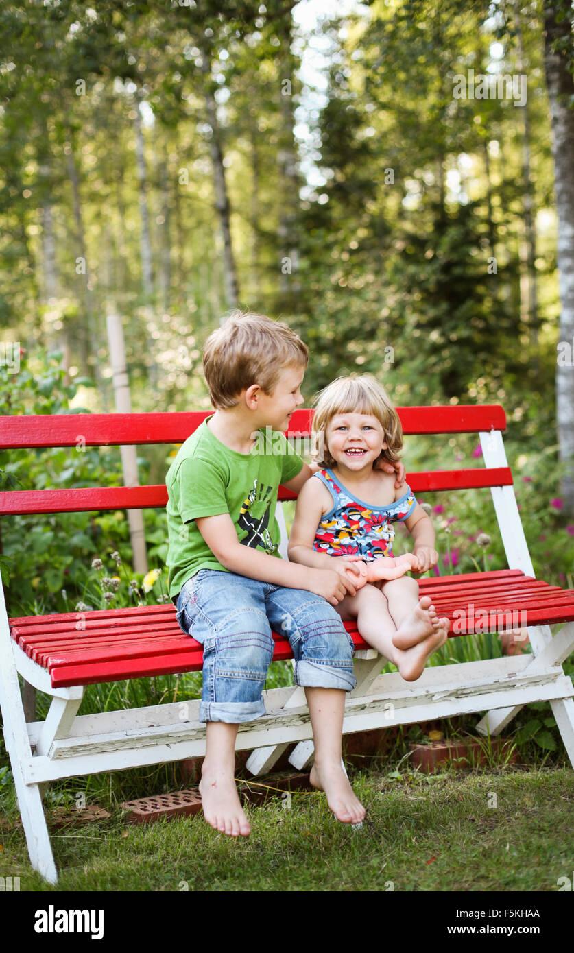 Suecia, Narke, Hallsberg, Boy (4-5) y (2-3) chica sentada en un banco Imagen De Stock