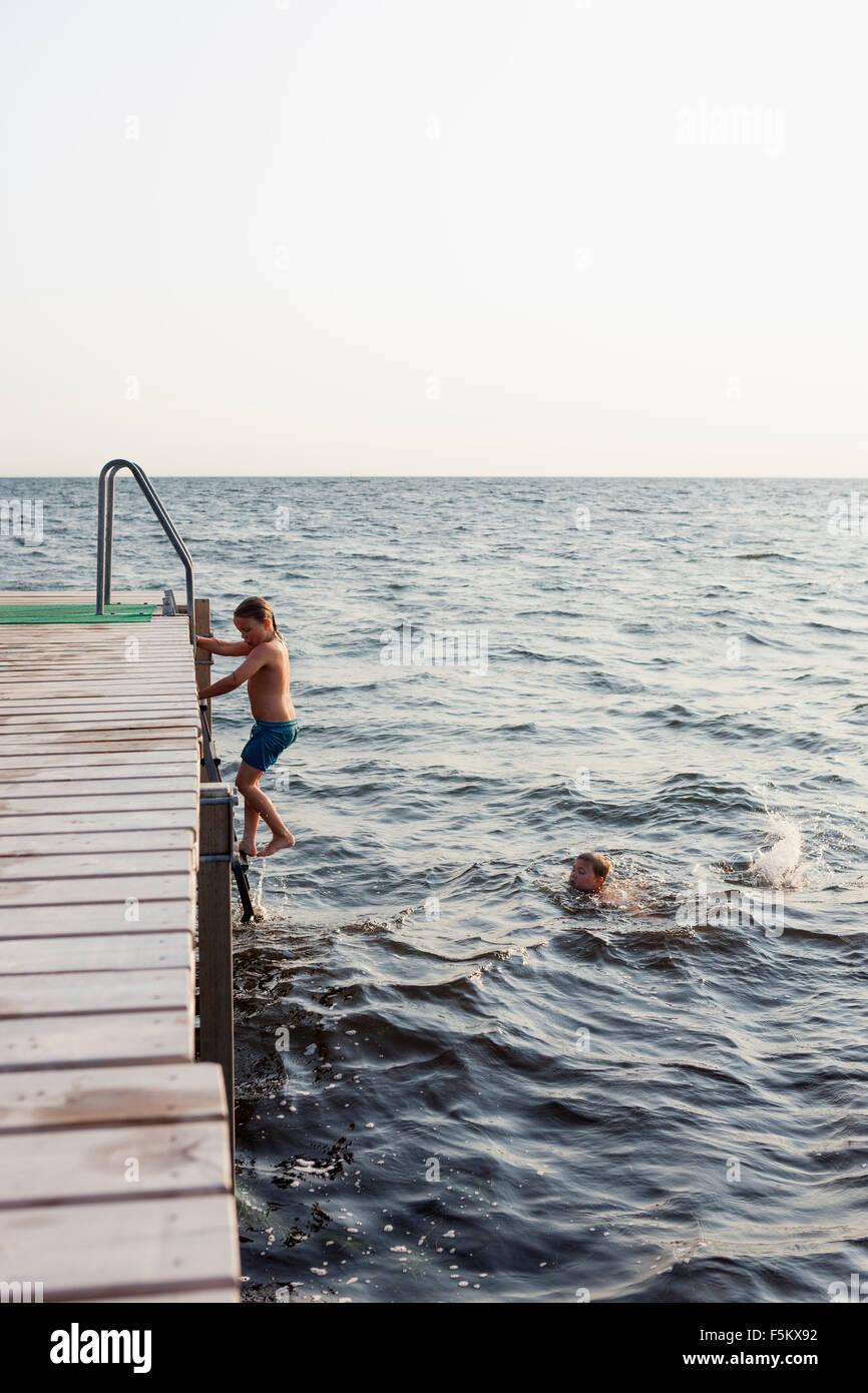 Suecia, Öland, Gronhogen, hermano de natación (10-11), mientras que su hermana (6-7) escalera Imagen De Stock