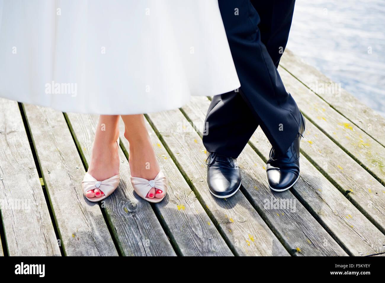 Suecia, Uppland Arholma, los pies del hombre y la mujer de pie en el muelle de madera Imagen De Stock