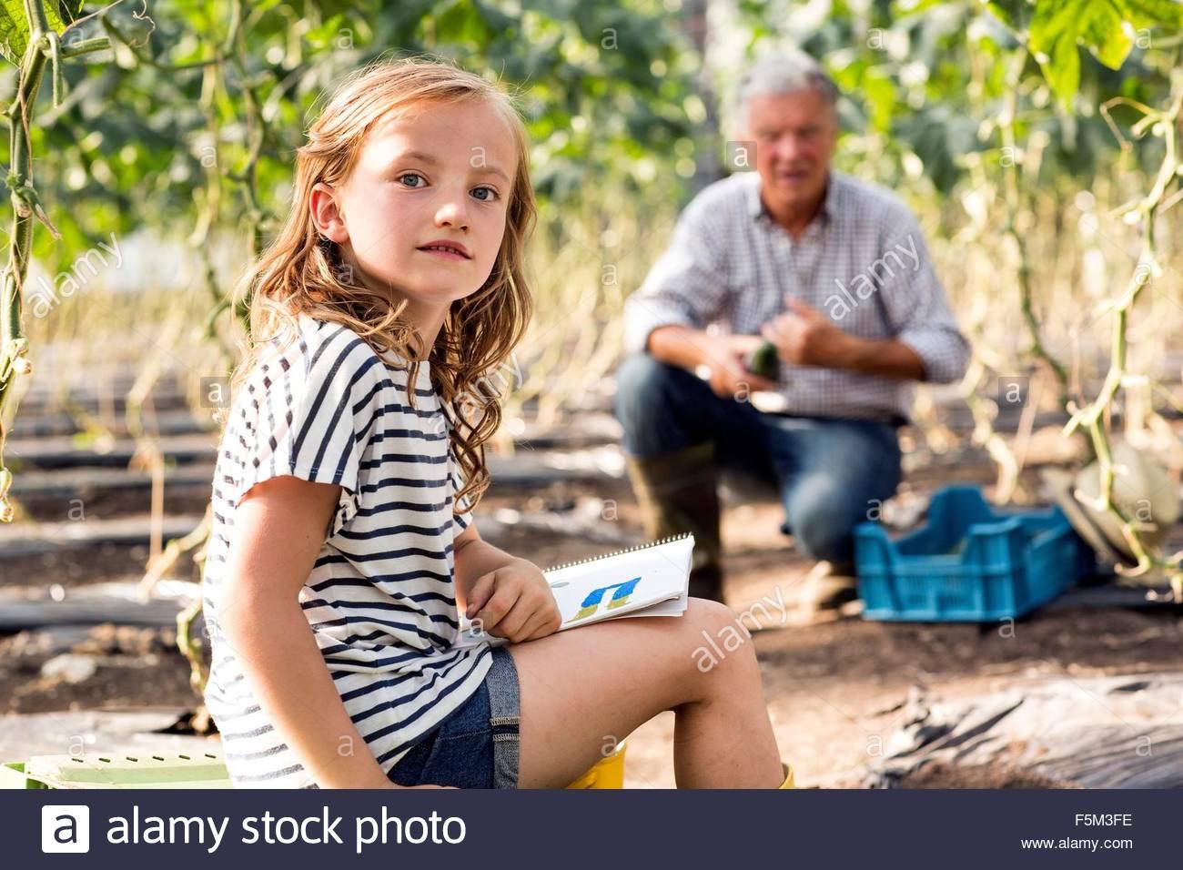 Chica sentada dibujo mientras abuelo trabaja mirando a la cámara Imagen De Stock