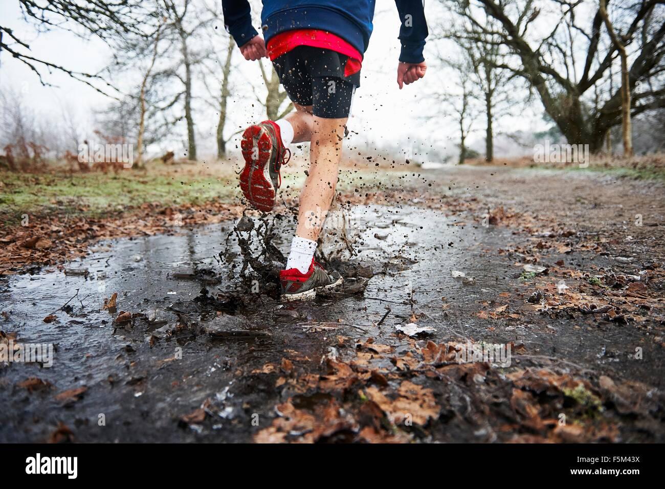 Vista trasera del adolescente corriendo a través de charco salpicaduras Imagen De Stock
