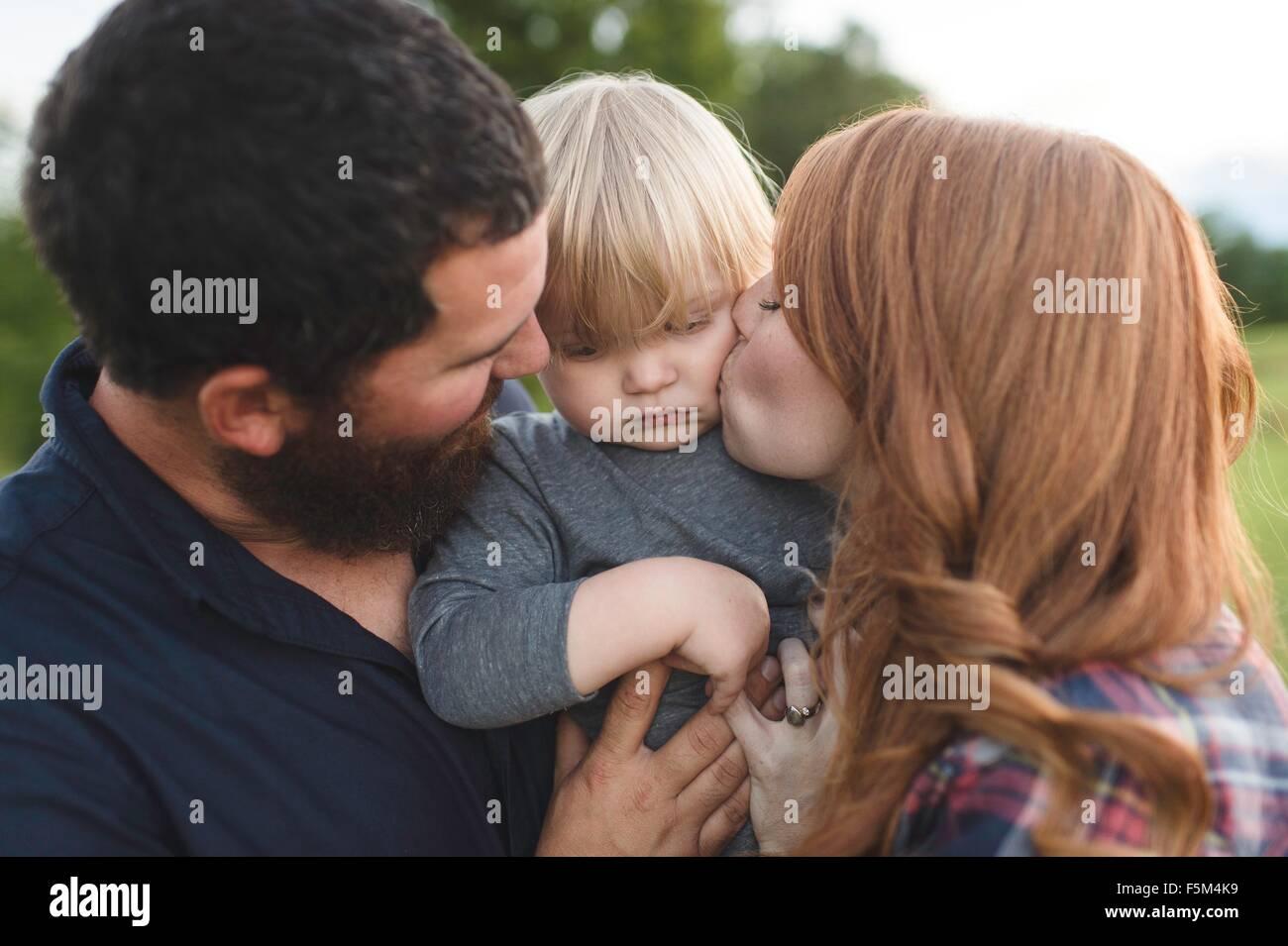 La madre y el padre mantiene joven hijo, exteriores Foto de stock