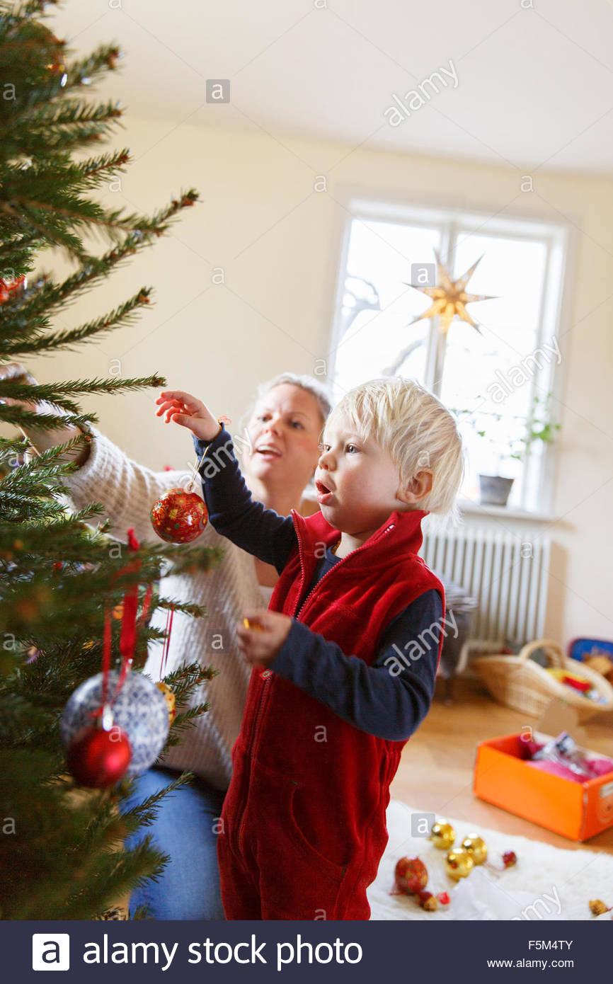 Suecia, madre con su hijo decorar árbol de navidad Imagen De Stock