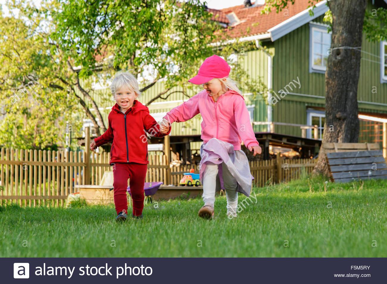Suecia, Sodermanland, Jarna, Niños (2-3, 4-5) jugando en el patio delantero Imagen De Stock