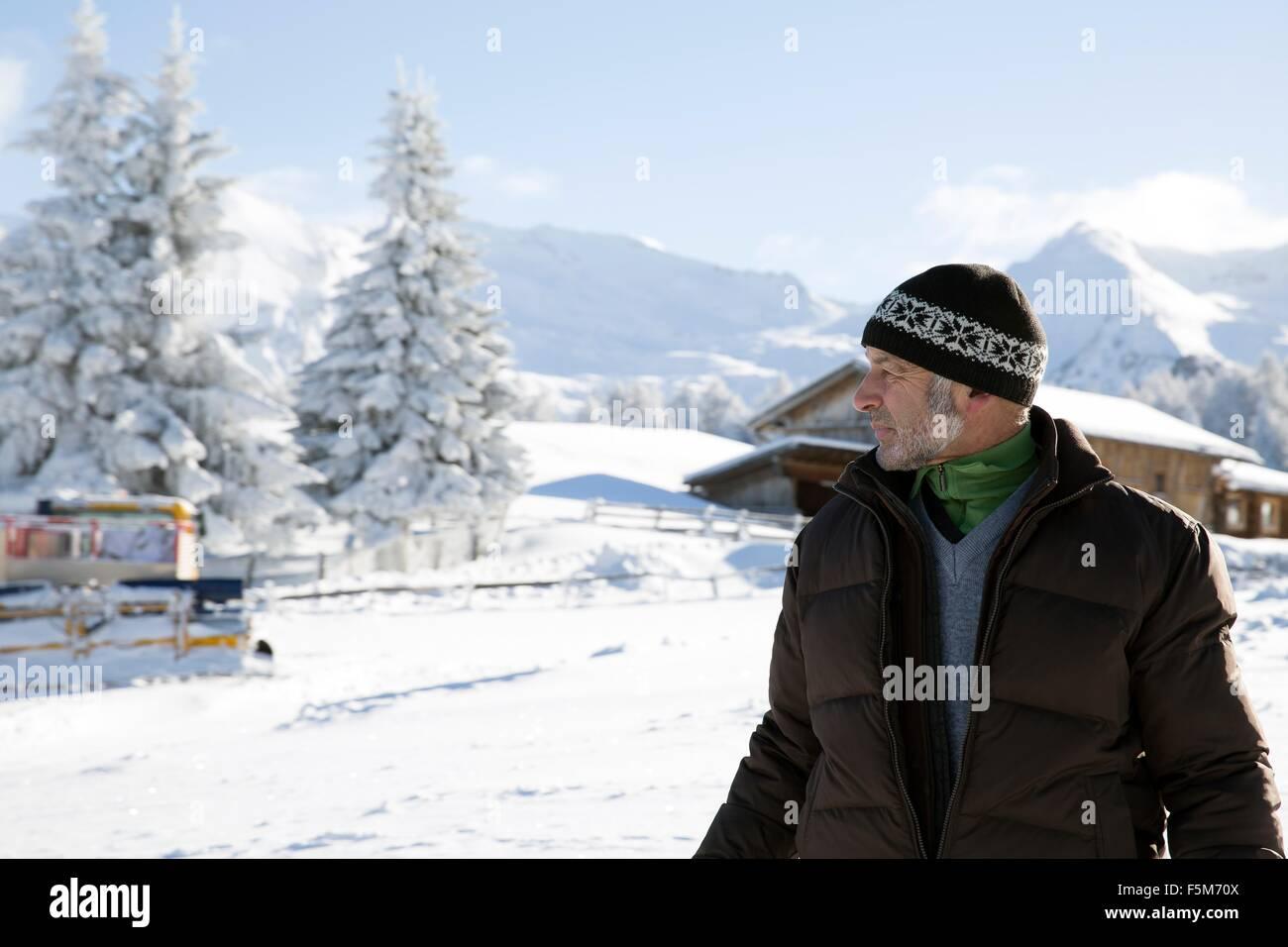 Cintura para arriba de altos árboles cubiertos de nieve y el hombre mirando lejos, Sattelbergalm, Tirol, Austria Imagen De Stock