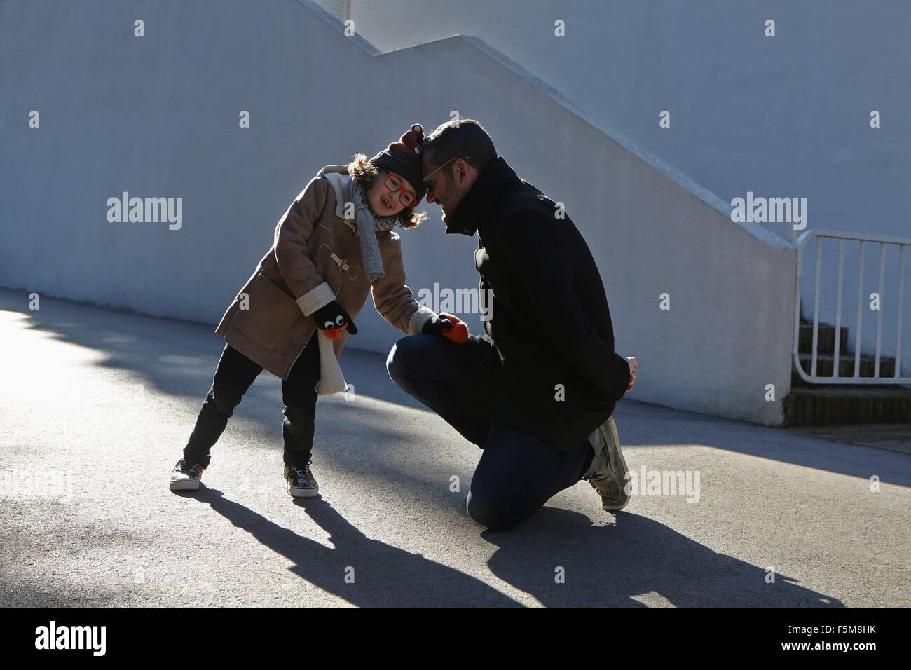 Padre e hija vistiendo duffle coat cabeza a cabeza en calle Imagen De Stock