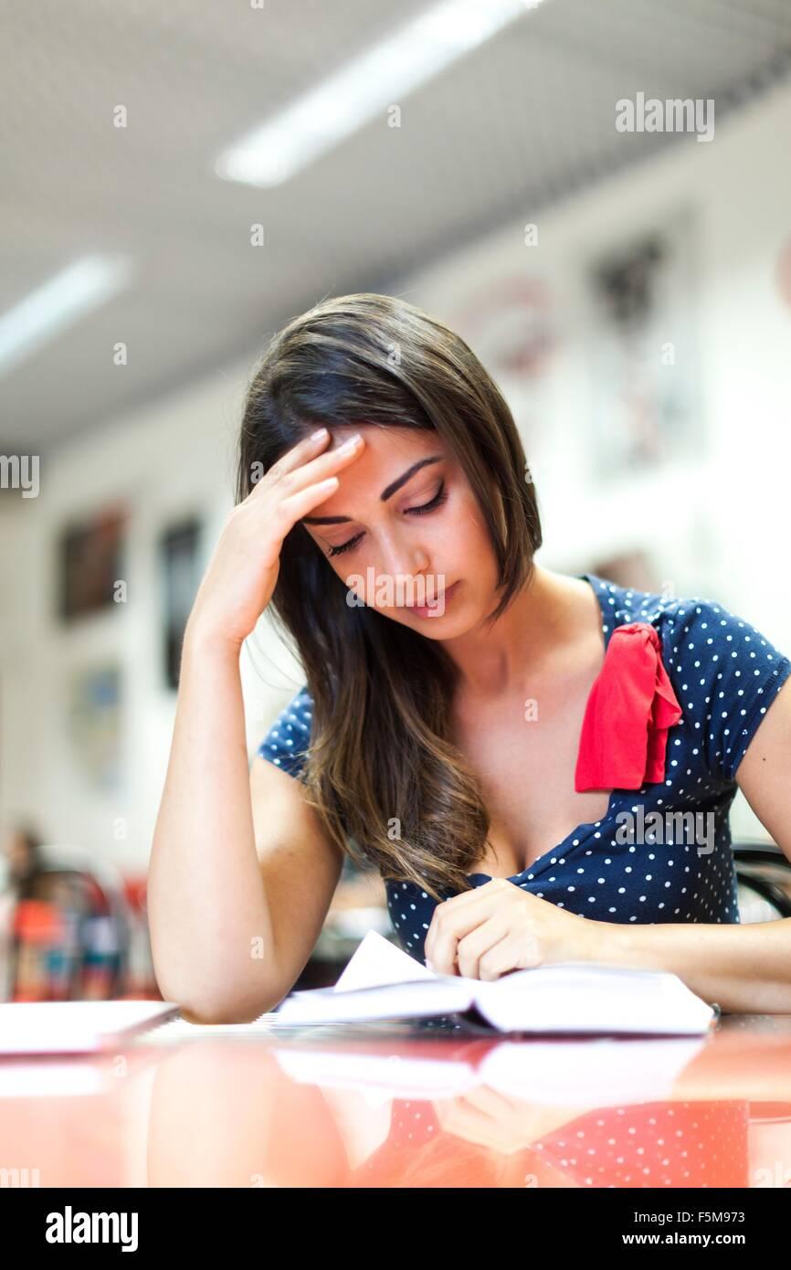 Mujer joven, sentado, estudiando Imagen De Stock