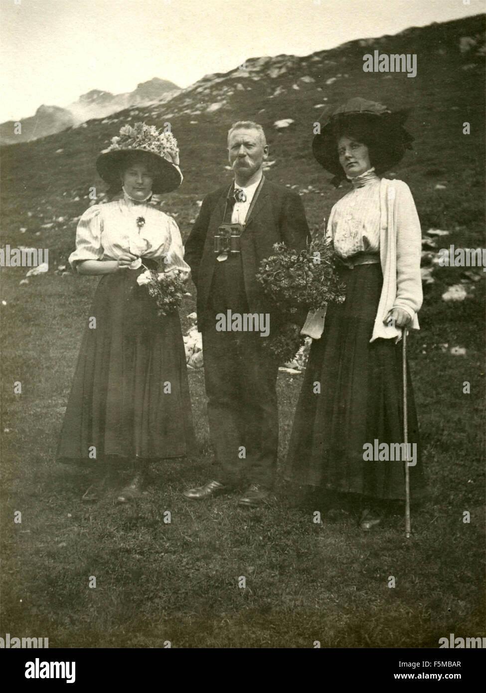 Un hombre con dos mujeres elegantes durante una caminata en las montañas, Italia Imagen De Stock