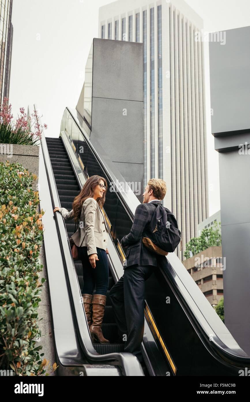 La empresaria y el hombre sube las escaleras mecánicas, Los Angeles, EE.UU. Imagen De Stock
