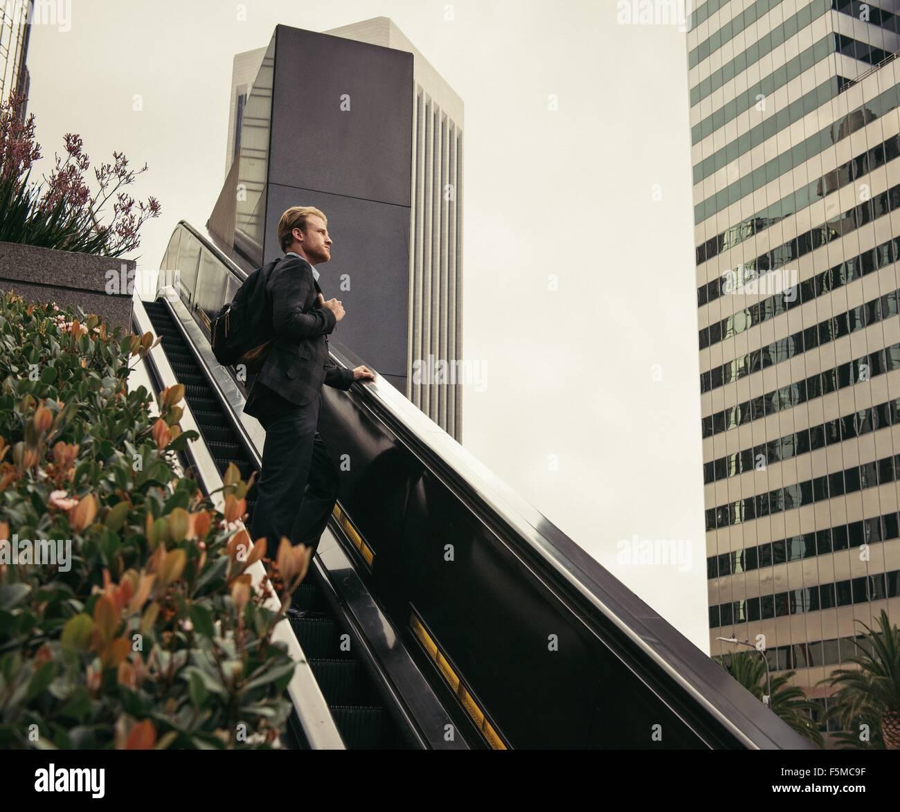 Empresario subiendo las escaleras mecánicas, Los Angeles, EE.UU. Imagen De Stock