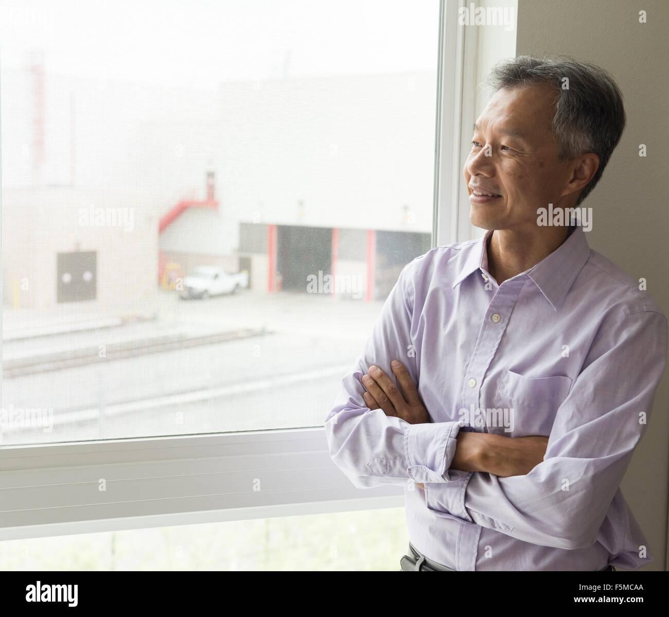 Cintura para arriba de hombre maduro, mirando por la ventana con los brazos cruzados Imagen De Stock