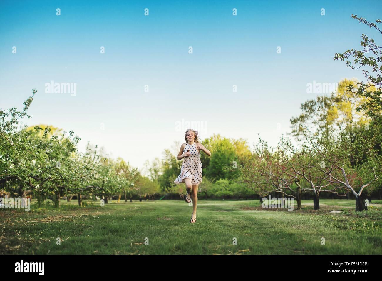 Vista frontal de la longitud completa de la joven mujer vistiendo camisetas sin mangas vestido corriendo a través Imagen De Stock