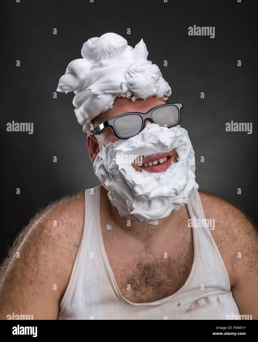 Extraño hombre sonriente en gafas con espuma de afeitar en su rostro y en su cabeza sobre fondo gris Foto de stock