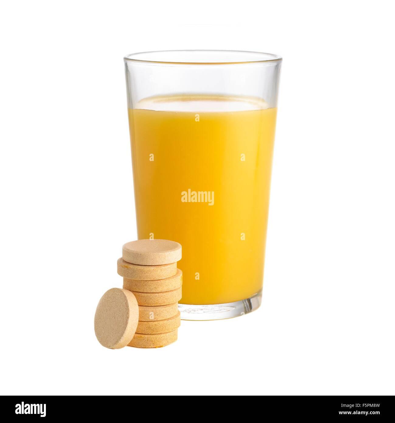 El jugo de naranja y tabletas de vitamina c contra un fondo blanco. Imagen De Stock