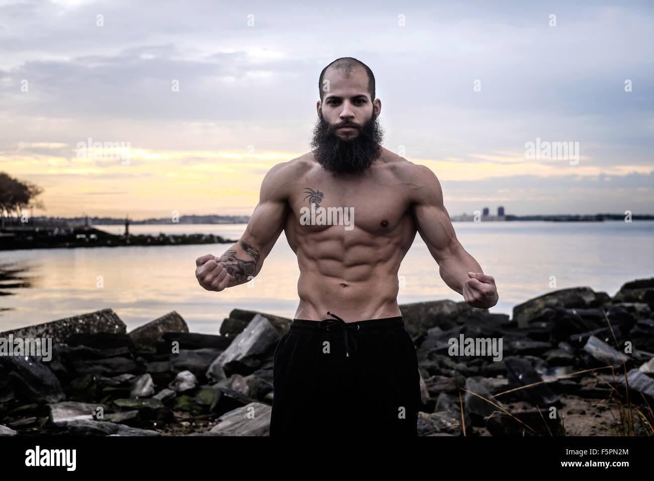 Hombre Barbado se flexiona los músculos abdominales al amanecer en una playa rocosa. Imagen De Stock