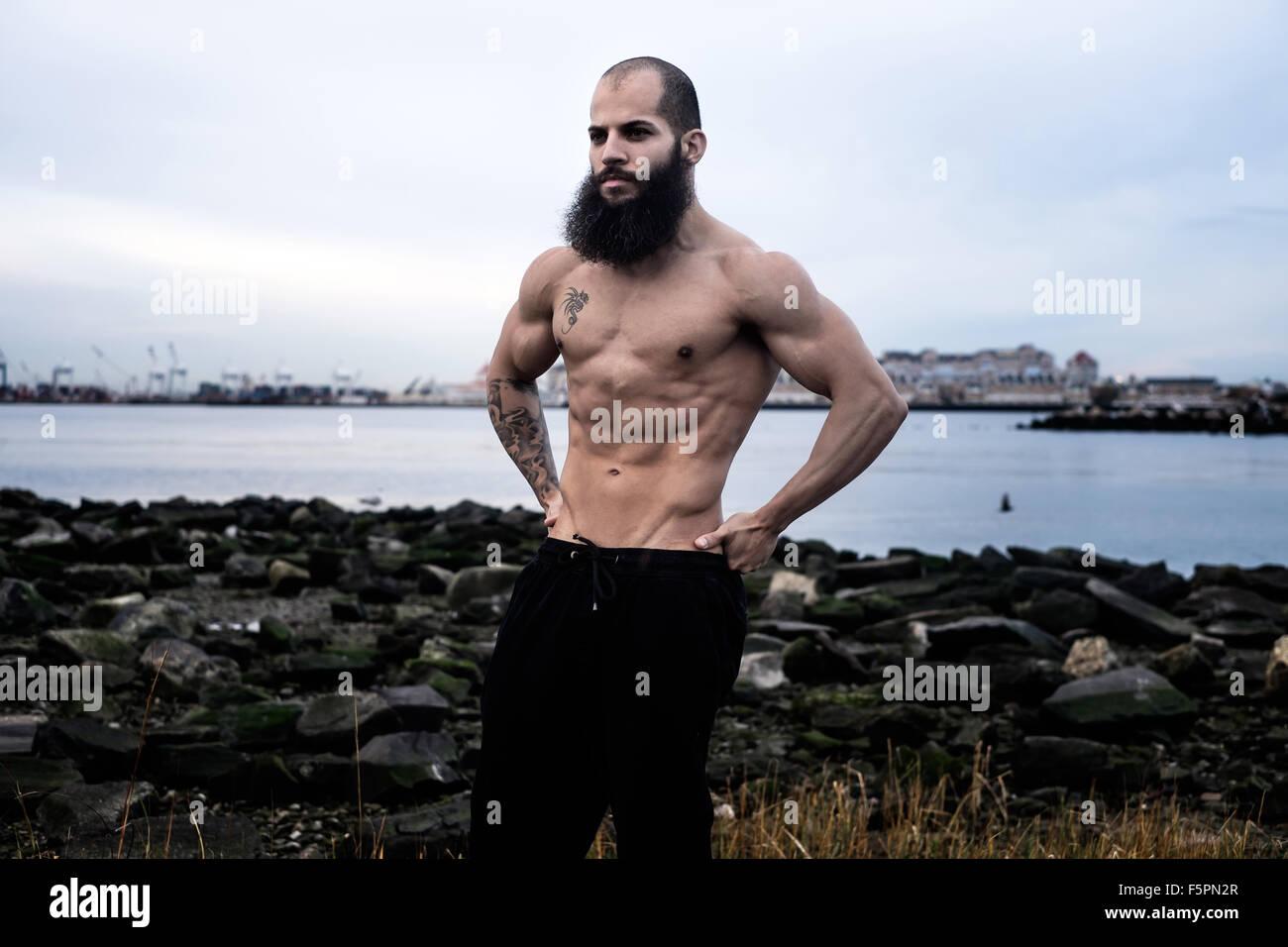 Hombre sin camisa se flexiona los músculos abdominales en una playa rocosa Imagen De Stock