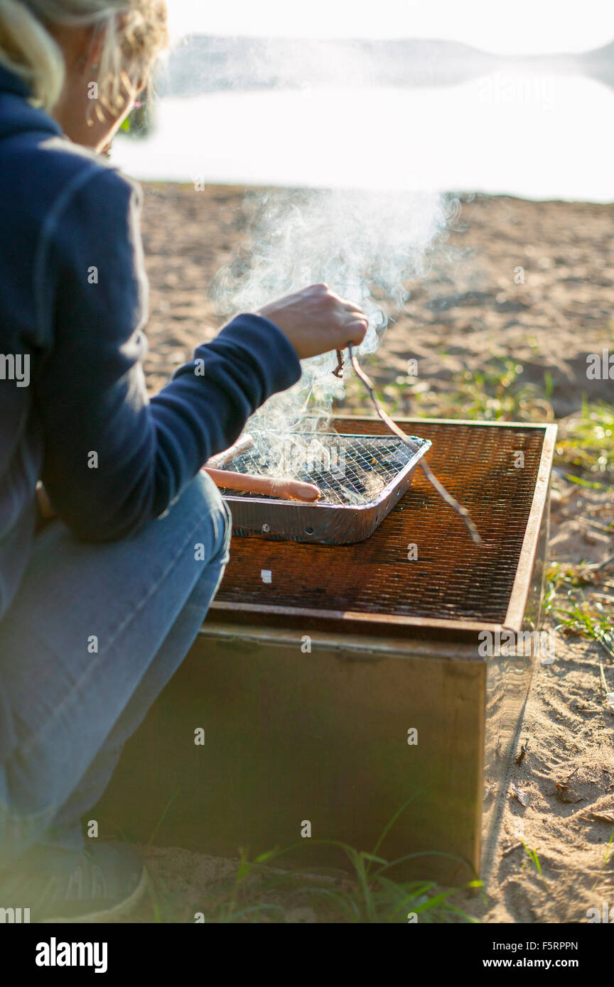 Suecia, Vastergotland, Lerum, Mujer cocinando por el lago Foto de stock