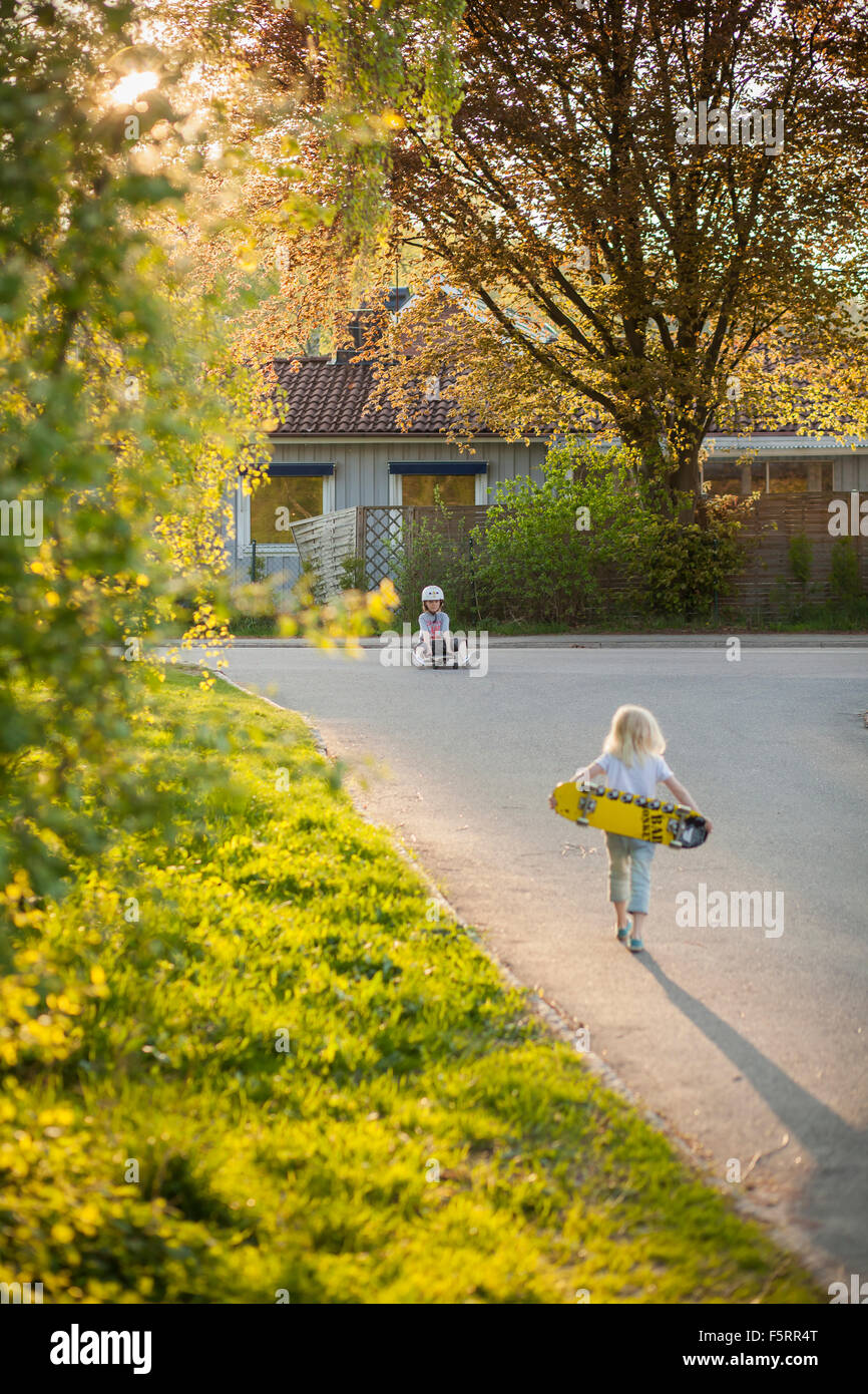 Suecia, Vastergotland, Lerum, Chica (6-7) caminando a boy (8-9) con el monopatín Imagen De Stock