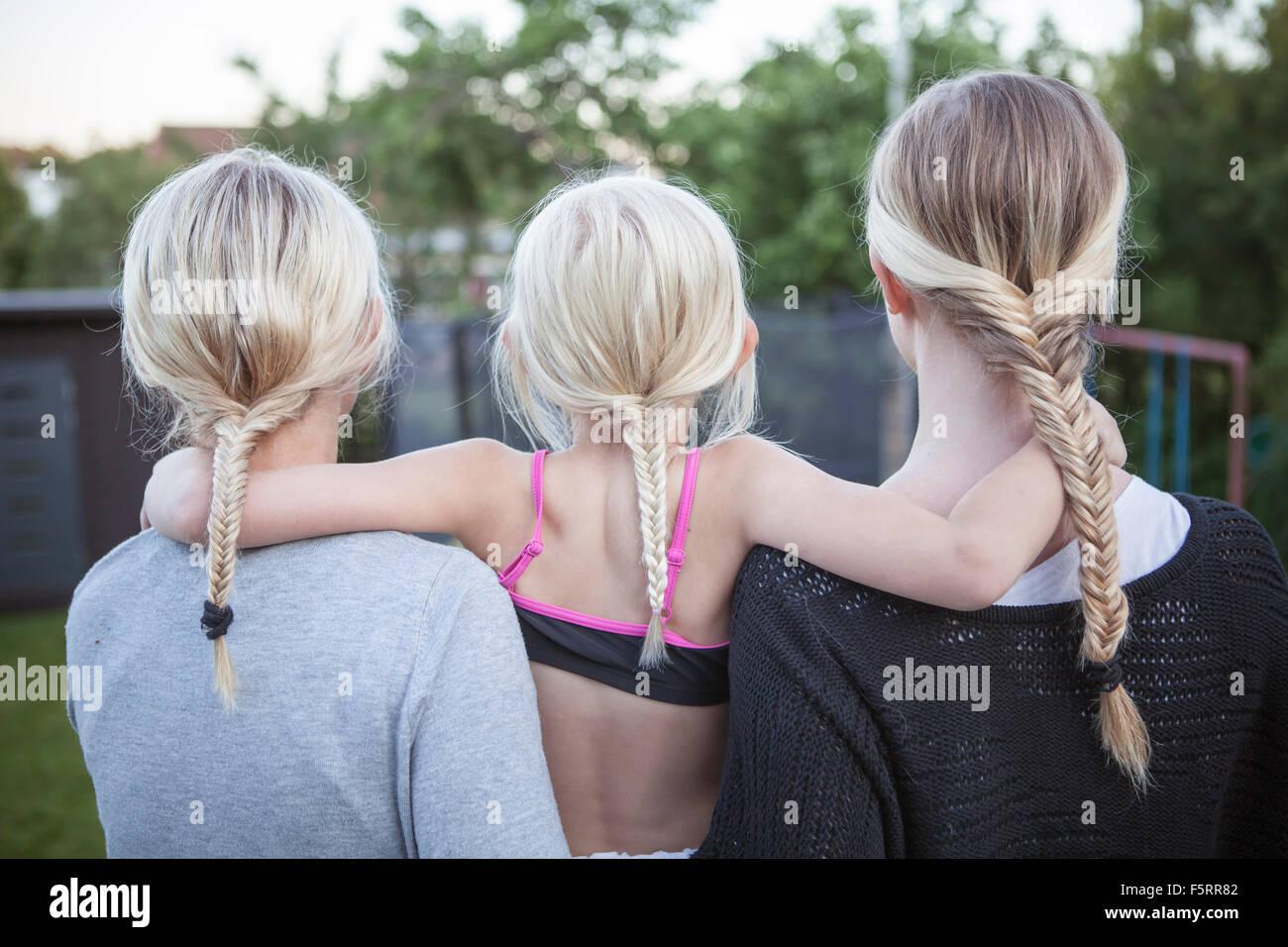 Suecia, Vastergotland, Lerum, vista trasera de las niñas (8-9, 16-17) con coleta trenzada de pie en el patio Imagen De Stock