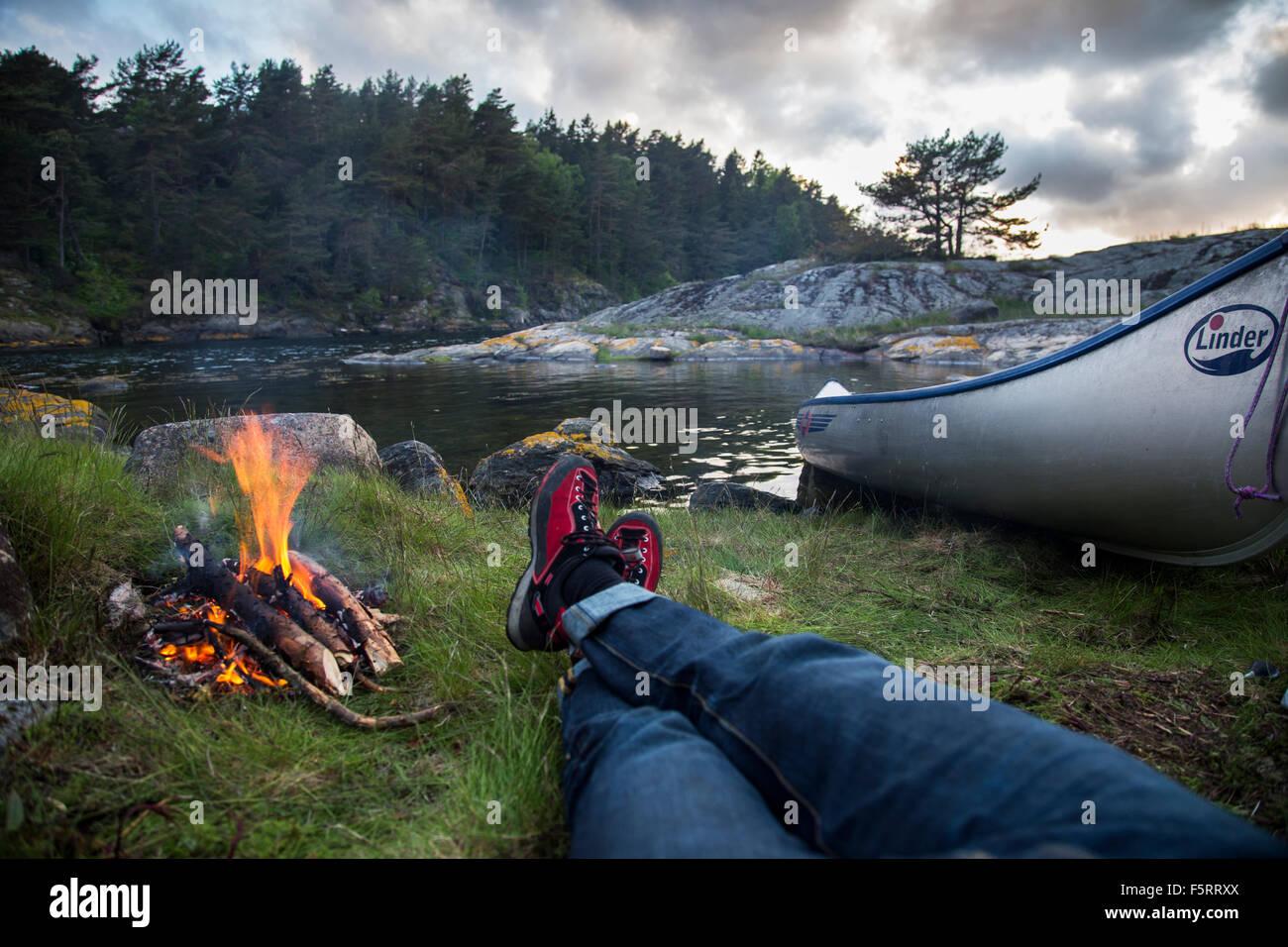 Suecia, Costa oeste, Bohuslan, Flato, perspectiva personal de hombre tumbado por fogata en riverbank Imagen De Stock