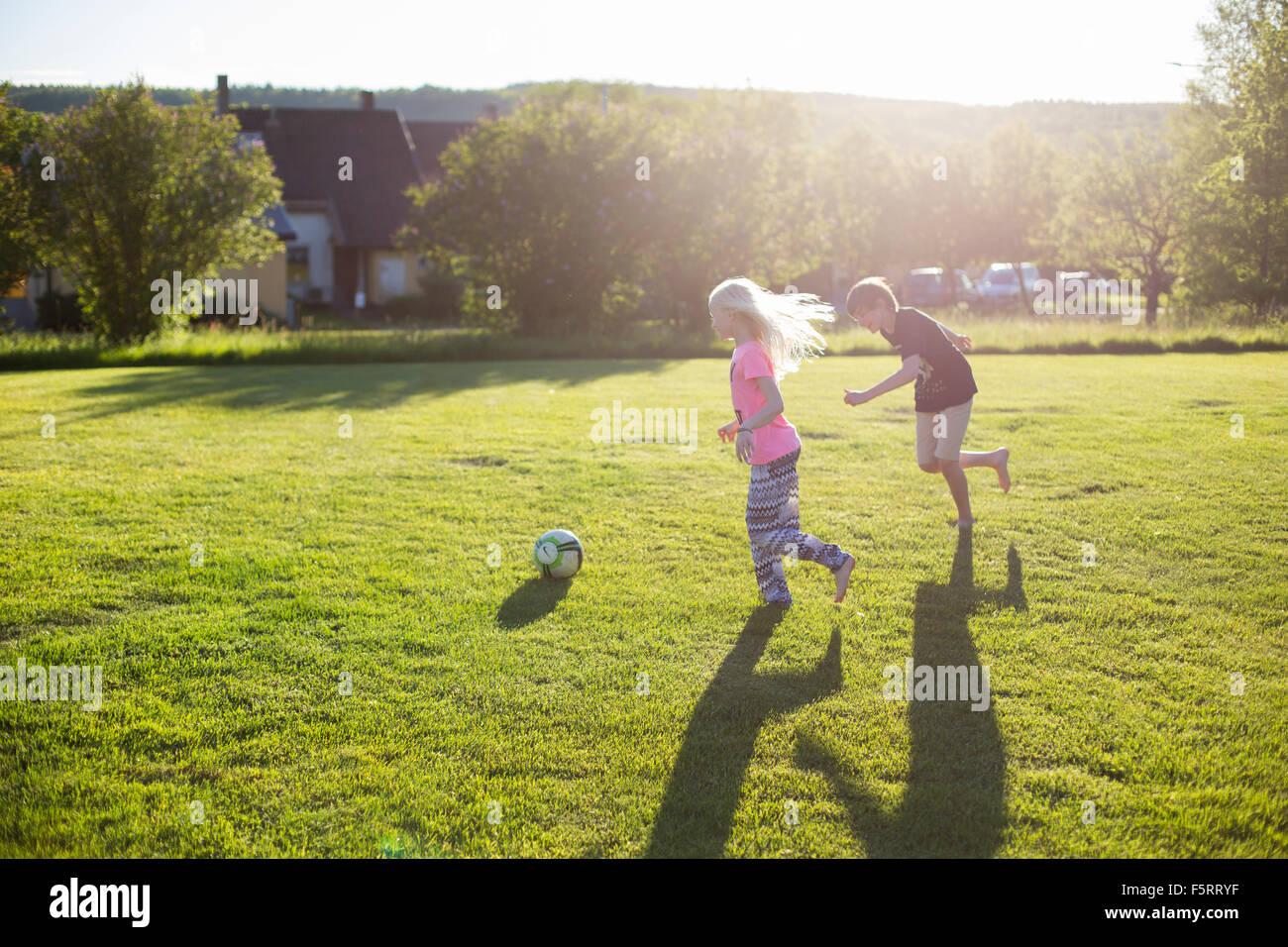 Suecia, Narke, Garphyttan, niña y niño (10-11) (12-13) jugando al fútbol en el jardín Foto de stock