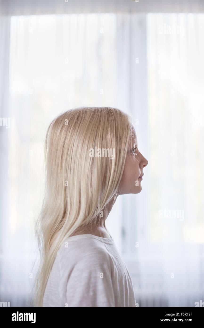 Suecia, vista lateral de la chica rubia (10-11) en la parte delantera de cortinas blancas Foto de stock
