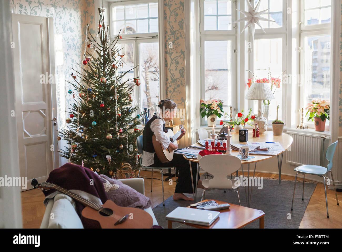 Suecia, Senior mujer tocando la guitarra en el salón Imagen De Stock