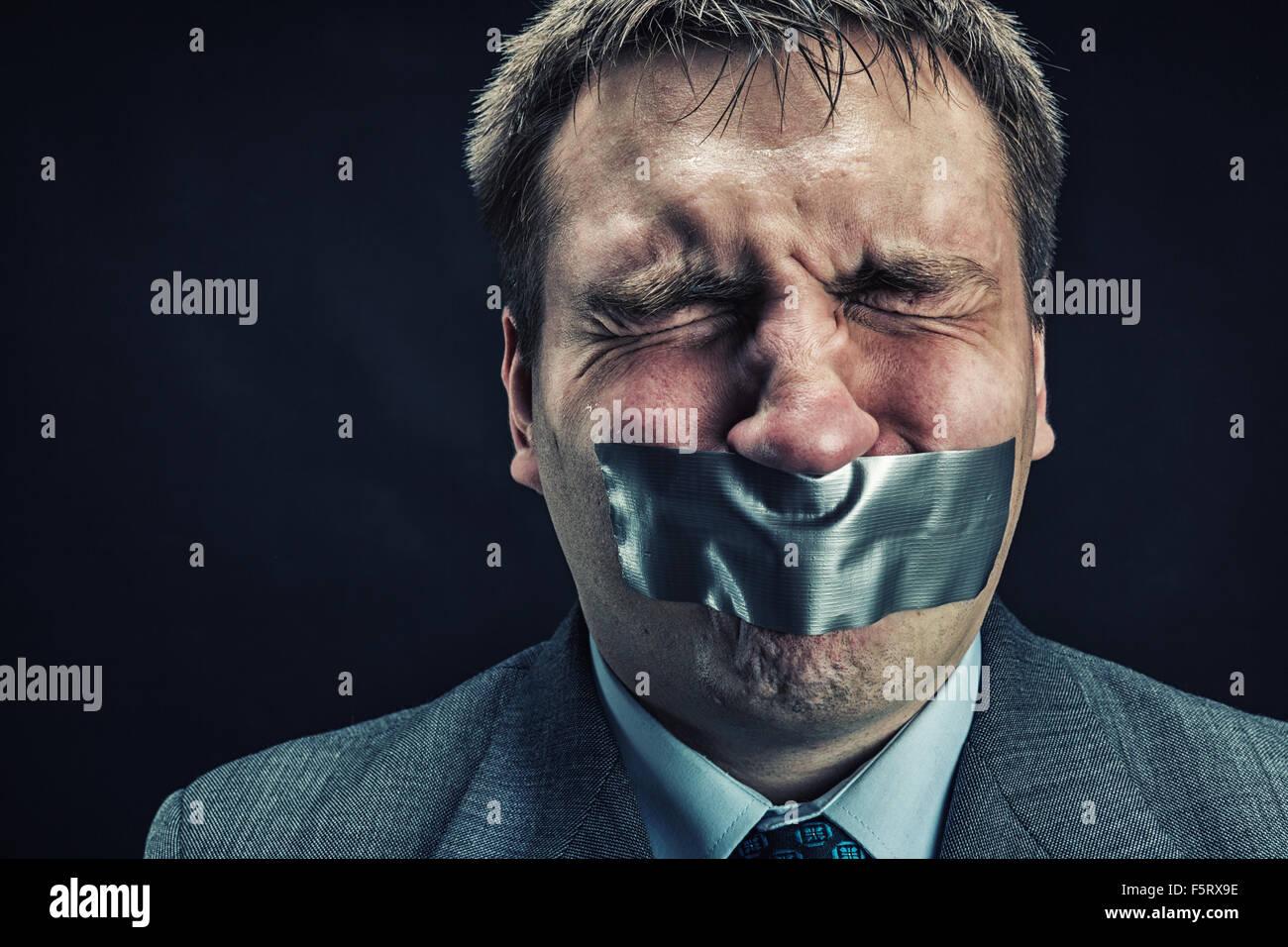 El hombre con la boca cubierta con cinta de enmascarar prevenir discurso, aislados en negro Imagen De Stock