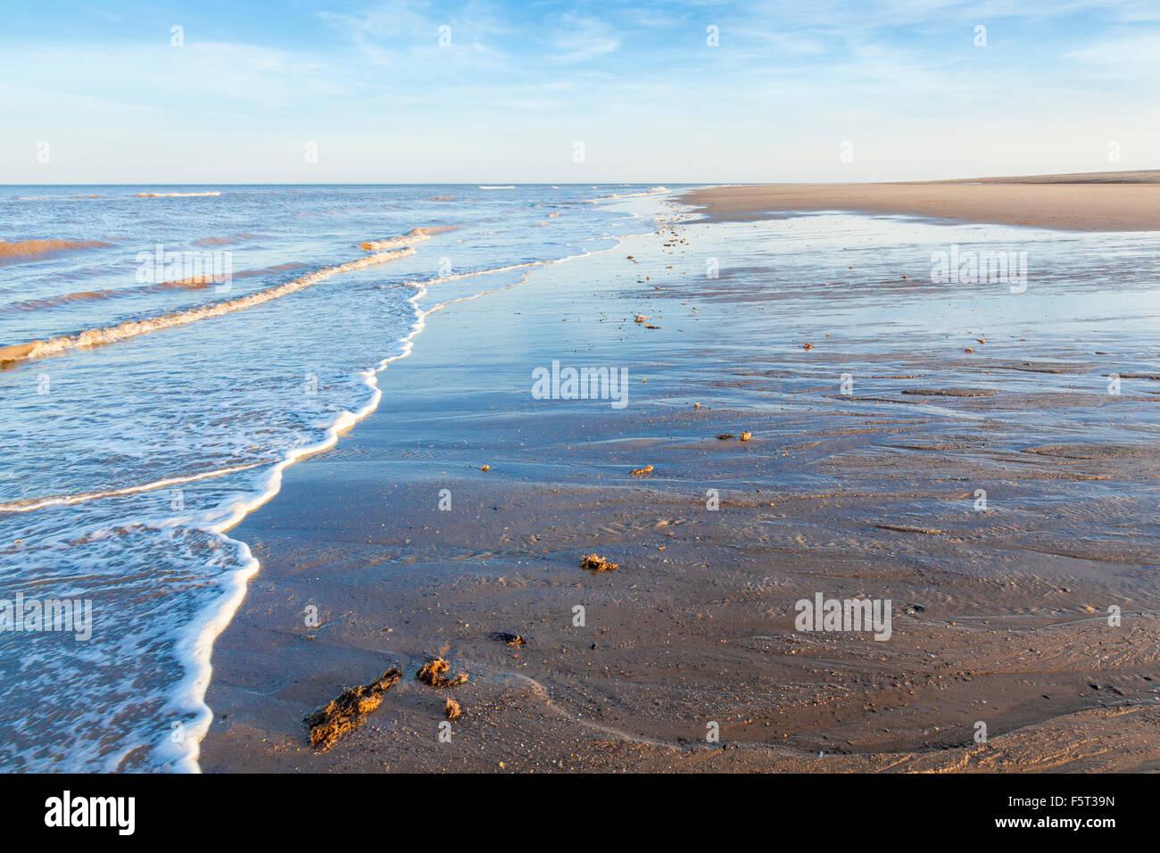El flujo y reflujo de un mar en calma. Pequeñas olas durante una marea baja en una tarde de verano en Gibraltar, Foto de stock