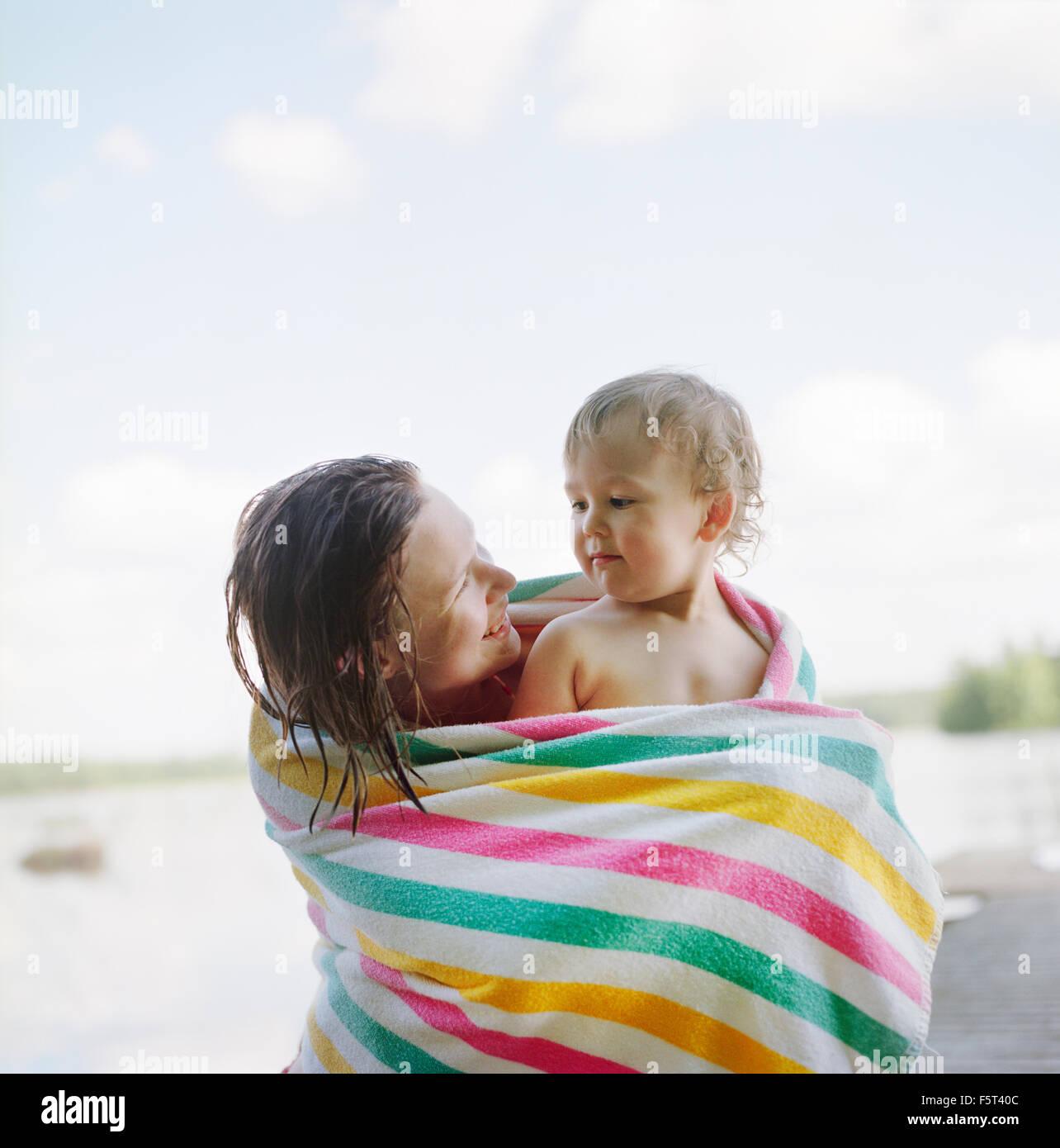 Finlandia, Uusimaa, Lapinjarvi, madre e hija (2-3) envuelto en toalla Imagen De Stock